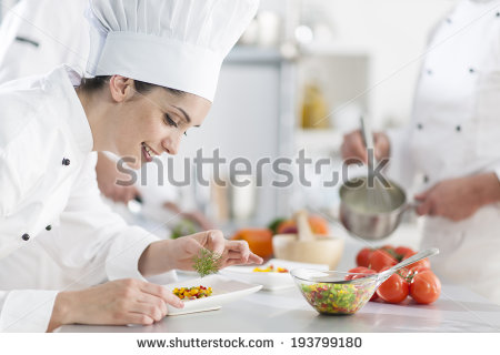 stock-photo-closeup-on-a-female-chef-preparing-a-dish-her-team-in-the-background-193799180